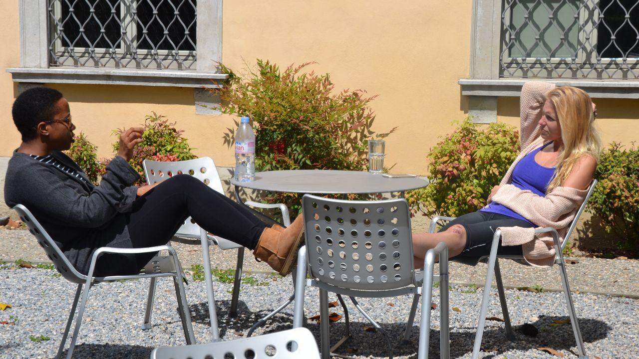 Students sit at a table on the grounds of Villa Maderni
